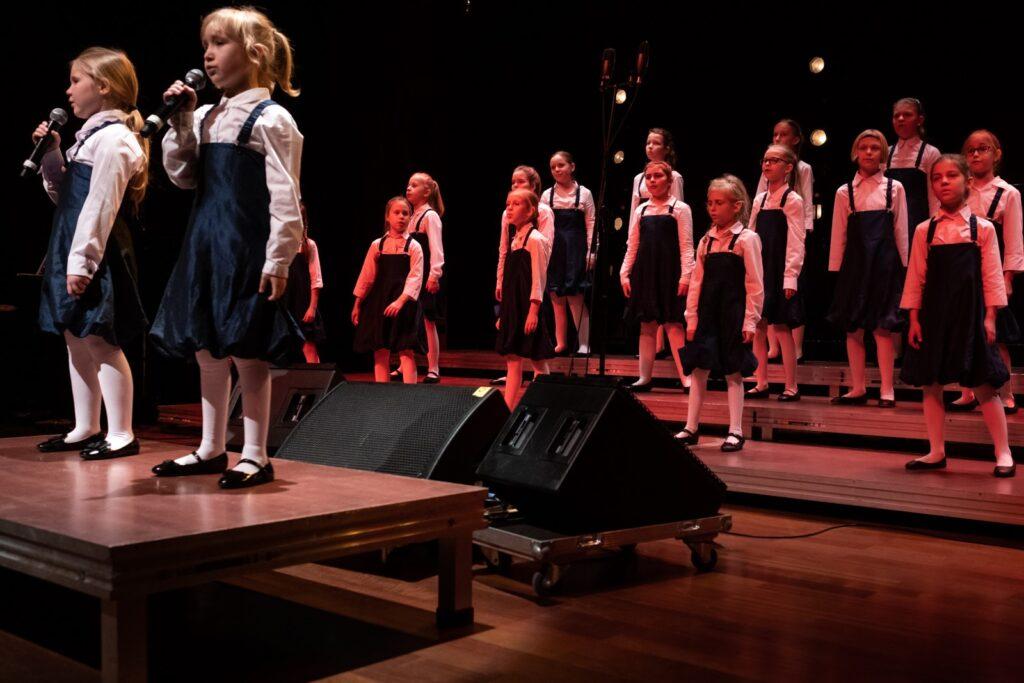 Fotografia przedstawia chór małych dziewczynek w białych bluzkach i granatowych sukienkach. Na pierwszym planie dwie z nich, na podwyższeniu, śpiewają do mikrofonów, pozostałe śpiewają za nimi. Scena oświetlona jest różnokolorowym światłem. Fotografię wykonano w sali Wielkiej CK ZAMEK.