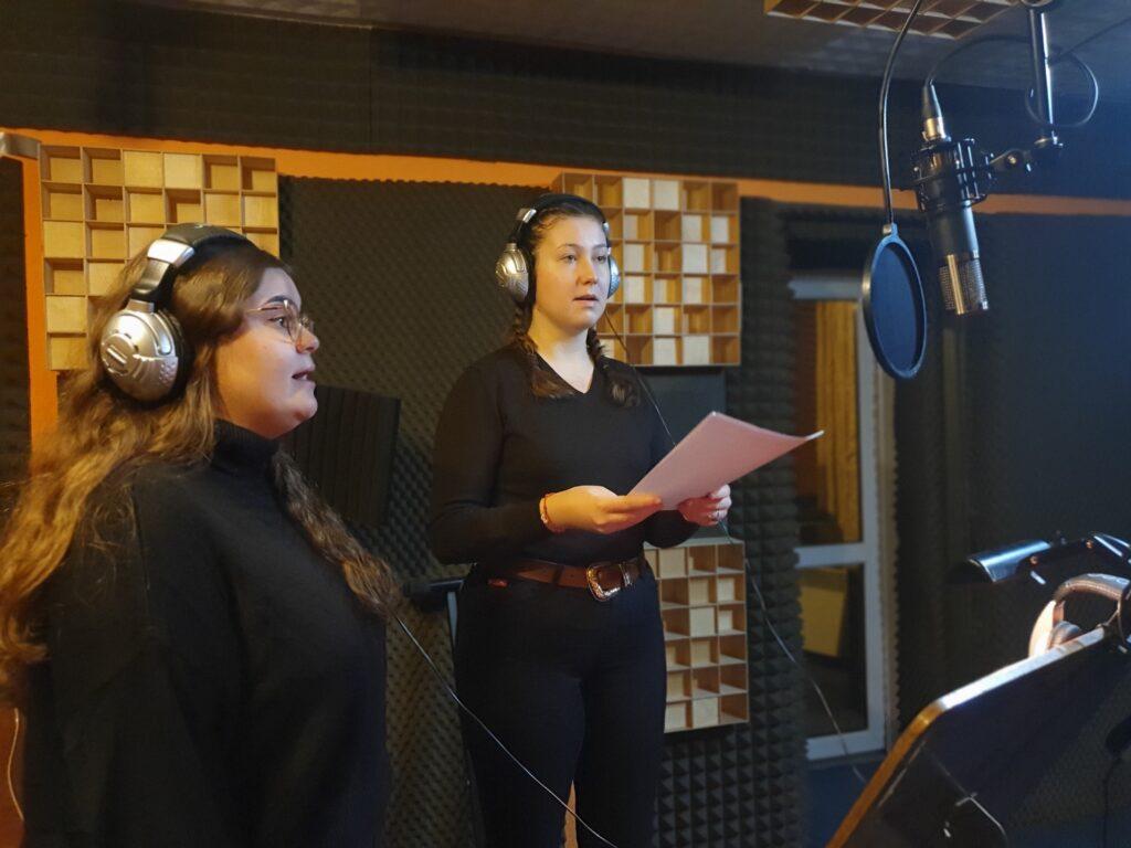 Fotografia przedstawia studio nagrań. Przed mikrofonem stoją dwie śpiewające dziewczyny w słuchawkach na uszach. Ubrane są na czarno. Jedna z nich trzyma w rękach tekst lub nuty. Obie patrzą na mikrofon. Przed nimi stoi pulpit. Za śpiewaczkami znajduje się ściana pokryta elementami wygłuszającymi dźwięk.