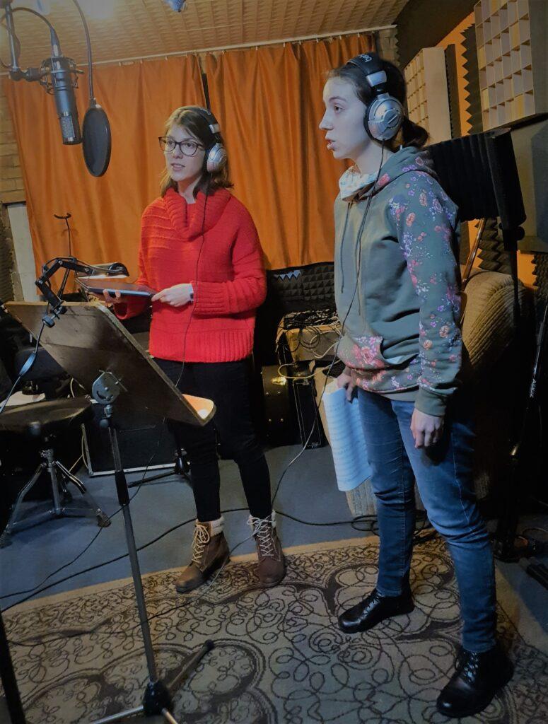 Fotografia przedstawia studio nagrań. Przed mikrofonem stoją dwie śpiewające dziewczyny w słuchawkach na uszach. W rękach trzymają tekst lub nuty, ale z nich nie korzystają. Wokół widać typowe elementy wyposażenia studia: kable, pulpit, statyw. Śpiewaczki stoją na wzorzystym dywanie.
