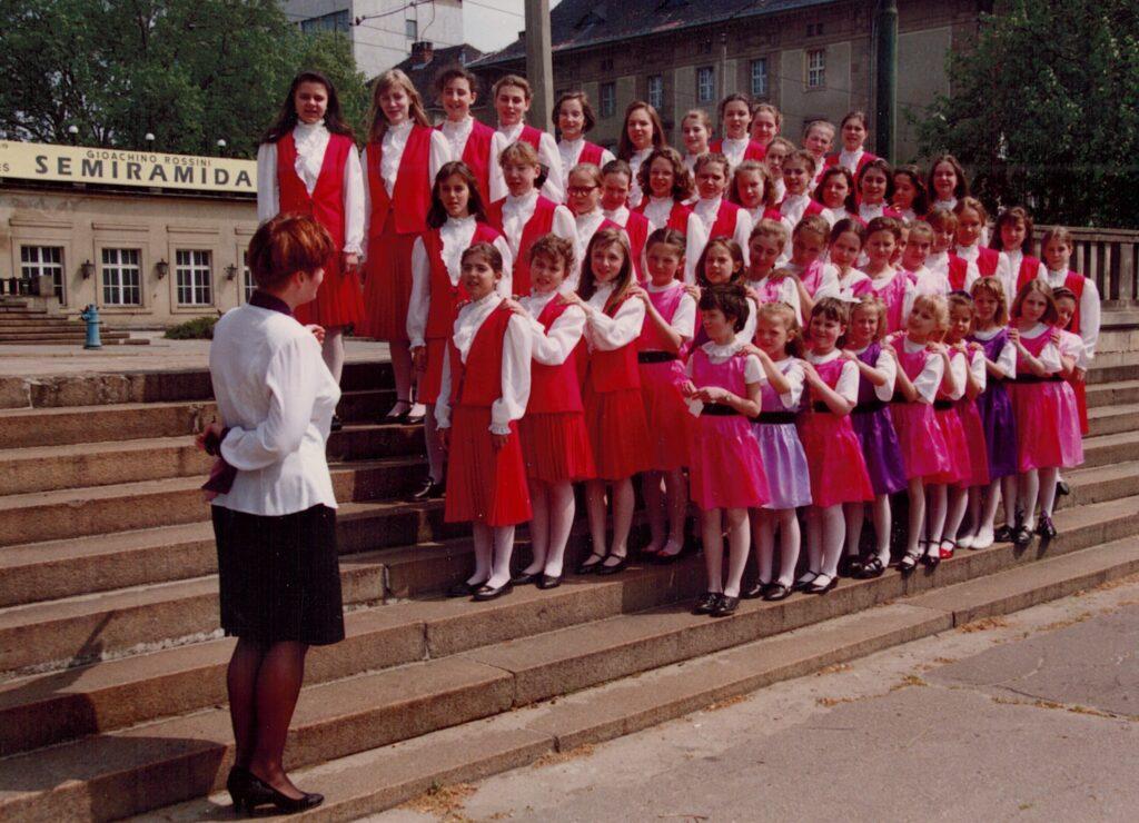 Na kamiennych schodach przed budynkiem Arkadii w Poznaniu stoi grupa dziewcząt w czerwonych spódniczkach, białych bluzkach i czerwonych kamizelkach. W pierwszym rzędzie znajdują się młodsze dziewczynki w kolorowych sukienkach. Wszystkie patrzą na kobietę w czarno-białym kostiumie stojącą przodem do nich, a tyłem do obiektywu. Kobieta wykonuje gest dyrygenta.