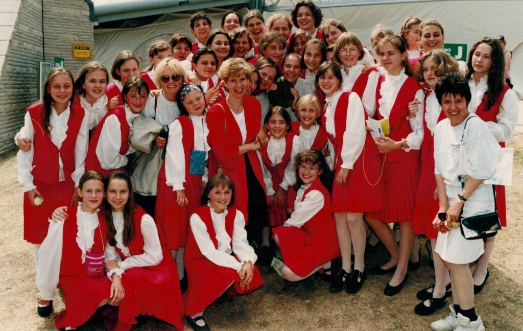 Grupa kilkudziesięciu dziewcząt w czerwono-białych kostiumach pozuje w letnim plenerze. Wszystkie się uśmiechają. Wśród nich znajduje się kilka, również uśmiechniętych kobiet.