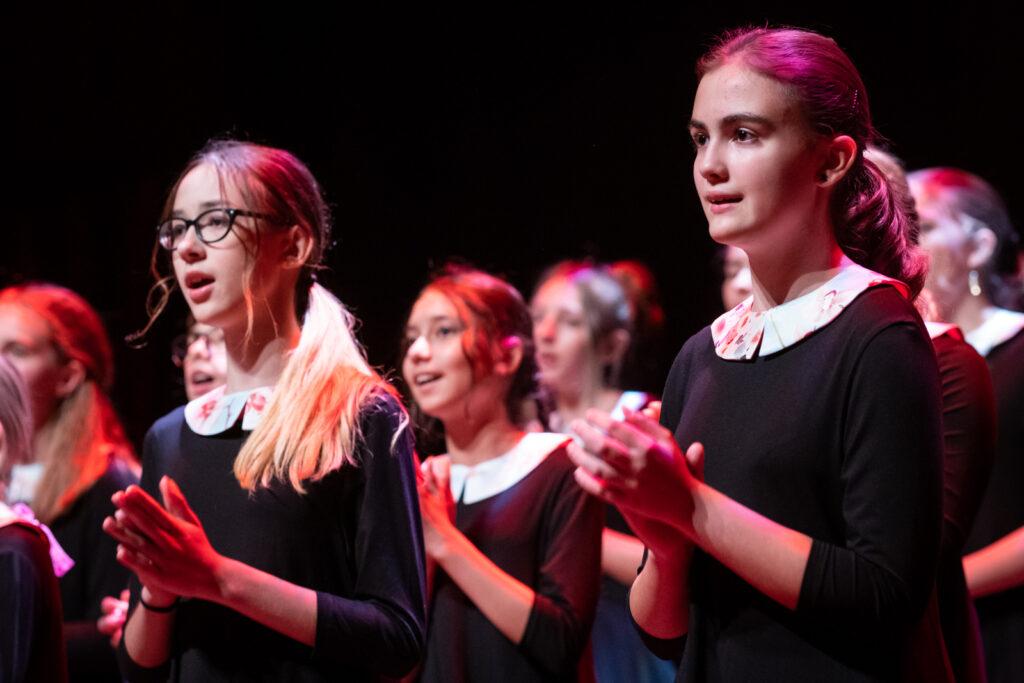 Na pierwszym planie znajdują się dwie śpiewające dziewczęta. Dłonie mają złożone jak do klaskania. Dziewczynka po lewej nosi okulary. W tle, nieco rozmazane ukazane są pozostałe chórzystki. Wszystkie ubrane są w ciemno-granatowe sukienki z białymi kołnierzykami w kwiaty.
