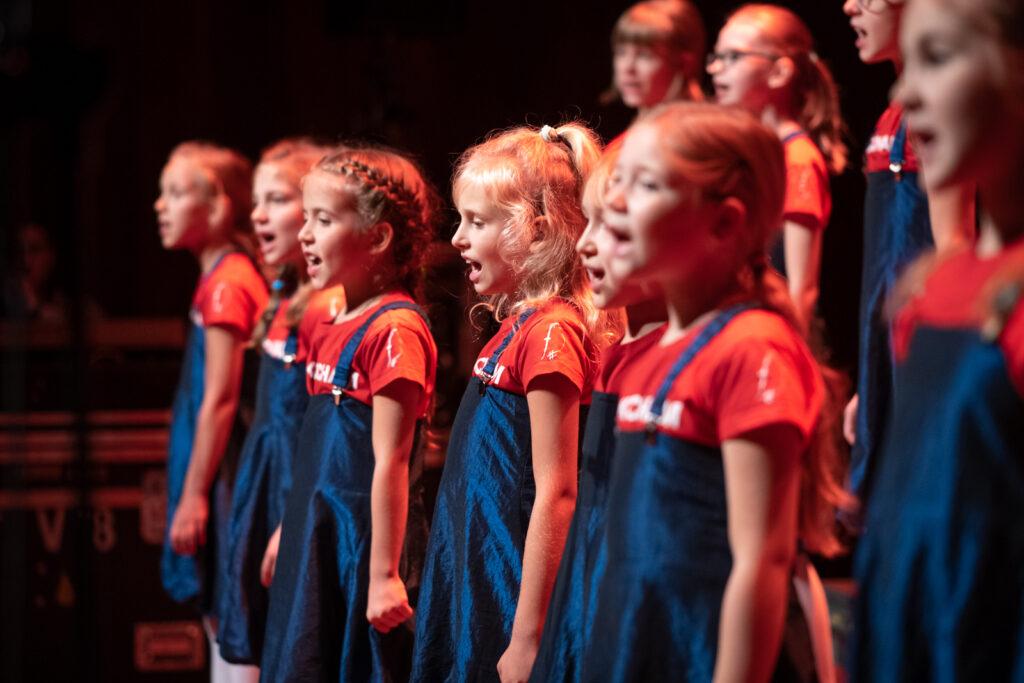 Na fotografii widzimy śpiewające dziewczynki w czerwonych koszulkach z logo Skowronków na rękawach, wpuszczone w niebieskie sukienki. Wszystkie skupione są na śpiewie.