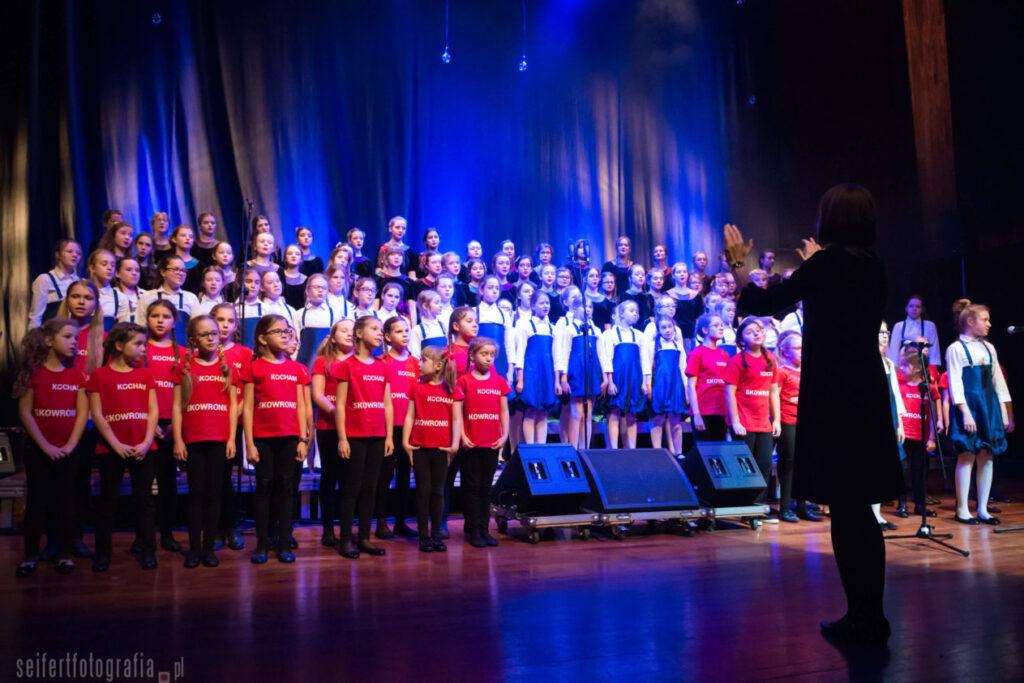 Na scenie Sali Wielkiej CK ZAMEK stoi grupa dziewcząt w różnym wieku. Przed nimi, tyłem widoczna jest sylwetka dyrygentki. Dziewczęta ubrane są w różne stroje, w zależności od wieku. Najmłodsze – w pierwszym rzędzie – mają na sobie czerwone koszulki. Za nimi stoją dziewczynki ubrane w niebieskie sukienki i białe bluzki, a ostatnie rzędy zajmują najstarsze chórzystki w czarnych kostiumach. Na wszystkie postaci pada niebieskie światło sceniczne. Po prawej stronie fotografii zauważyć można solistkę stojącą przed mikrofonem. Dyrygentka daje znak do rozpoczęcia śpiewu.