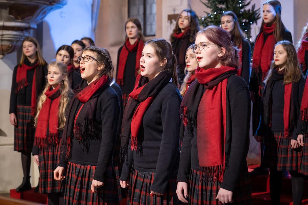 Fotografia przedstawia grupę dziewcząt podczas śpiewu. Wszystkie ubrane są w granatowe swetry i spódniczki w czerwono-granatową kratę. Na szyjach mają szale przechodzące z czerwieni w granat. W tle widać choinkę i mury starego kościoła.