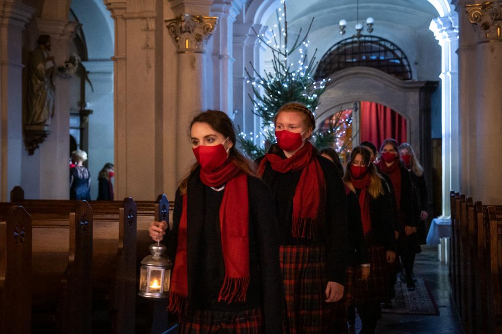 Na pierwszym planie widać dwoje dziewcząt przemierzających kościelną nawę. W świątyni panuje półmrok, w tle widać jasno oświetloną choinkę. Obie dziewczyny ubrane są w granatowe swetry i spódniczki w niebiesko-granatową kratę. Na szyjach mają zawieszone czerwone szale, a twarze zakrywają im czerwone maski. Pierwsza z nich niesie w prawej ręce zapaloną latarnię. Za nimi podążają pozostałe dziewczynki w takich samych strojach.