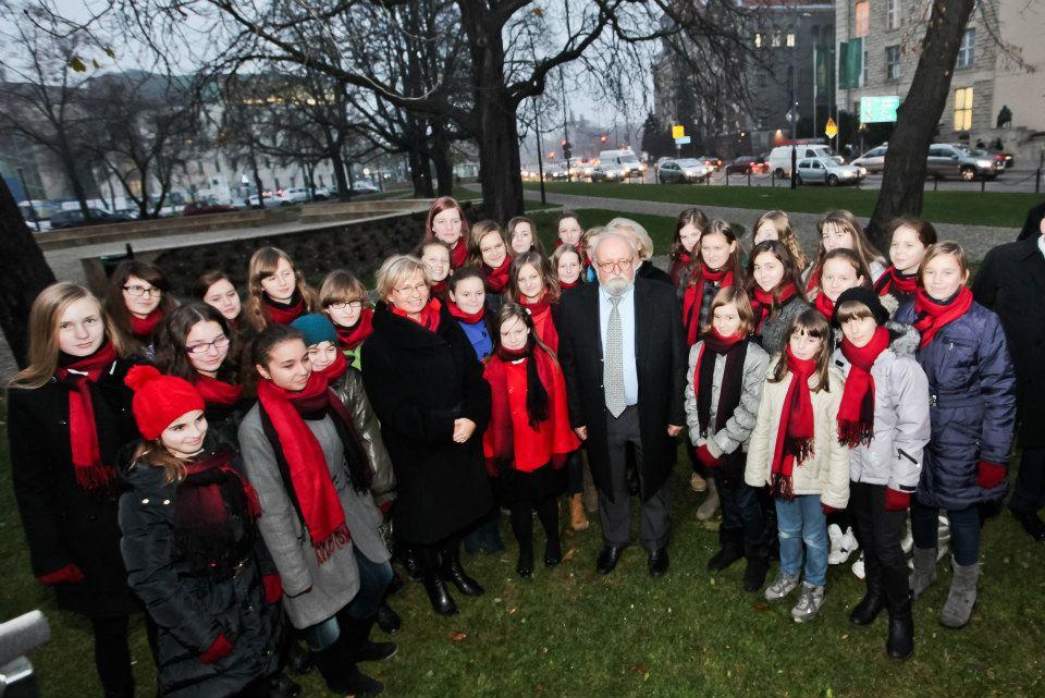 W centralnym punkcie fotografii stoi Krzysztof Penderecki  otoczony grupą dziewcząt. Dziewczynki ubrane są w zimowe kurtki i jednakowe czerwono-czarne szale. Po lewej stronie stoi kobieta. W tle widać skrzyżowanie ulic i budynek Zamku.