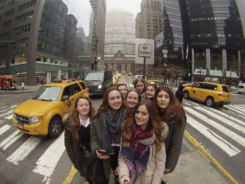 Grupa uśmiechniętych dziewcząt stoi na wysepce przejścia dla pieszych pomiędzy dwoma pasami jezdni. Po lewej i prawej stronie przejeżdżają żółte taksówki i inne samochody. W tle widać drapacze chmur Nowego Jorku.