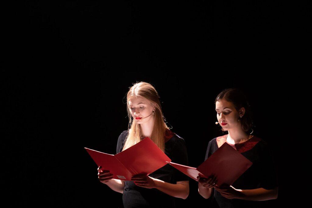 Z czarnego tła fotografii wyłaniają się dwie dziewczęce postaci. Obie oświetlone są ostrym światłem reflektorów scenicznych. Dziewczyna w centrum zdjęcia ma długie blond włosy i usta pomalowane na jaskrawoczerwony kolor. Trzyma czerwoną teczkę z tekstem. Nie widzimy jej oczu, gdyż skupione są na treści, również niewidocznego dla nas, programu koncertu. Dziewczyna po prawej, nieco słabiej oświetlona, wykonuje tę samą czynność. Różni się od koleżanki kolorem gładko zaczesanych włosów. Jest brunetką.
