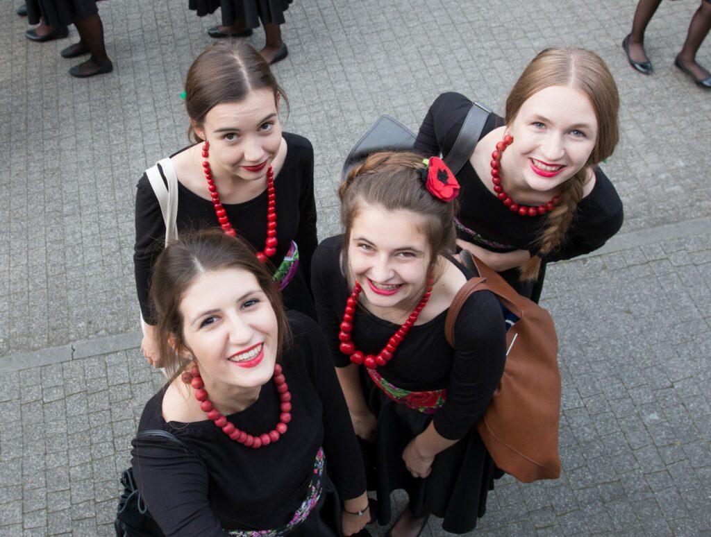 Ujęcie z góry przedstawia cztery dziewczęta, ubrane w czarne kostiumy i czerwone korale, które patrzą w górę i uśmiechają się. Jedna z dziewcząt ma wpięty we włosy czerwony kwiat. Zdjęcie zostało zrobione w plenerze.