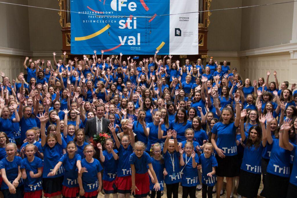 """Na scenie w Auli UAM stoi około dwustu dziewcząt w jednakowych niebieskich koszulkach z napisem """"trillme"""". Wszystkie mają uniesione ręce w radosnym pozdrowieniu. Wśród nich można dojrzeć uśmiechniętego mężczyznę ubranego w garnitur i trzymającego kwiaty. W tle, na organach wisi ogromny baner reklamujący festiwal."""