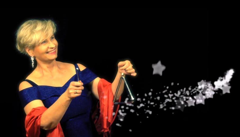 Po lewej stronie fotografii znajduje się uśmiechnięta kobieta w niebieskiej sukience i czerwonym szalu zawieszonym na przedramionach rąk. Ręce ma wyciągnięte przed siebie. W prawej dłoni trzyma metalową pałeczkę, a w lewej trójkąt. Wykonuje gest gry na tym instrumencie. Z trójkąta wydobywają się gwiazdy, które imitują dźwięk. Gwiazdy i gwiazdeczki lecą w prawą stronę, na skraj fotografii. W tę samą stronę patrzy radośnie kobieta trzymająca trójkąt. Tło zdaje się być czarniejsze niż najczarniejsze nocne niebo.