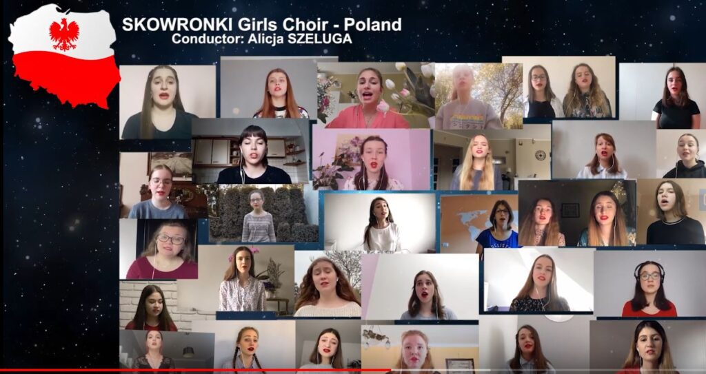 Zdjęcie stanowi zrzut ekranu komputera, na którym widzimy kilkadziesiąt okienek ze śpiewającymi dziewczętami. W lewym górnym rogu znajduje się wizerunek mapy Polski na biało-czerwonym tle, z czerwonym orłem w górnej, białej części. Obok, nad okienkami widnieje napis: SKOWRONKI Girls Choir. Conductor: Alicja Szeluga.