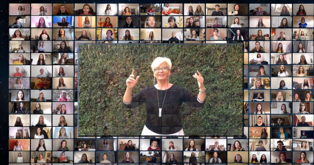 Fotografia jest zrzutem ekranu komputera. W centralnej części znajduje się kobieta na tle zielonego żywopłotu. Ręce ma uniesione w geście dyrygenckim. Wygląda na radosną. Nosi okulary, a na szyi zawieszony ma srebrny wisior z prostokątnym elementem u dołu. Ubrana jest w czarną bluzkę i białą spódnicę. Wokół postaci dyrygentki, na całym ekranie widać około sto małych okienek z wizerunkami śpiewających dziewcząt.