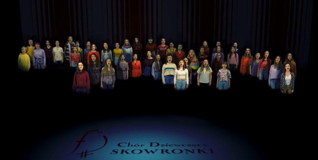 """Panoramiczna fotografia przedstawia chór dziewcząt zwrócony w stronę obiektywu. Dziewczęta stoją obok siebie w taki sposób, że tworzą układ przypominający skrzydła ptaka. Skrzydła te rozpostarte są na przestrzeni całego zdjęcia od lewej do prawej strony. Chórzystki ubrane są w kolorowe stroje bez wyraźnego, wspólnego motywu. Wszystkie śpiewają. Podłoga spowita jest czarną mgłą, przez co śpiewaczki wyglądają jak zjawy unoszące się nad mroczną, kosmiczną przestrzenią. Przed nimi, na podłodze, w miejscu rozświetlonym słabym niebieskim światłem, dostrzec można wizerunek czerwonego ptaka z napisem: """"Chór Dziewczęcy Skowronki""""."""