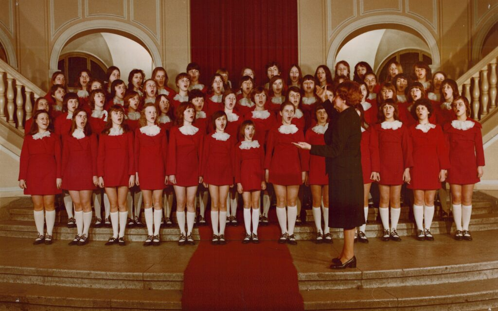 Na marmurowych schodach w zabytkowym pomieszczeniu śpiewa chór dziewcząt. Dziewczęta stoją w czterech rzędach i ubrane są w czerwone kostiumy z białymi kołnierzykami oraz białe podkolanówki. Przed nimi stoi dyrygentka ubrana na czarno.