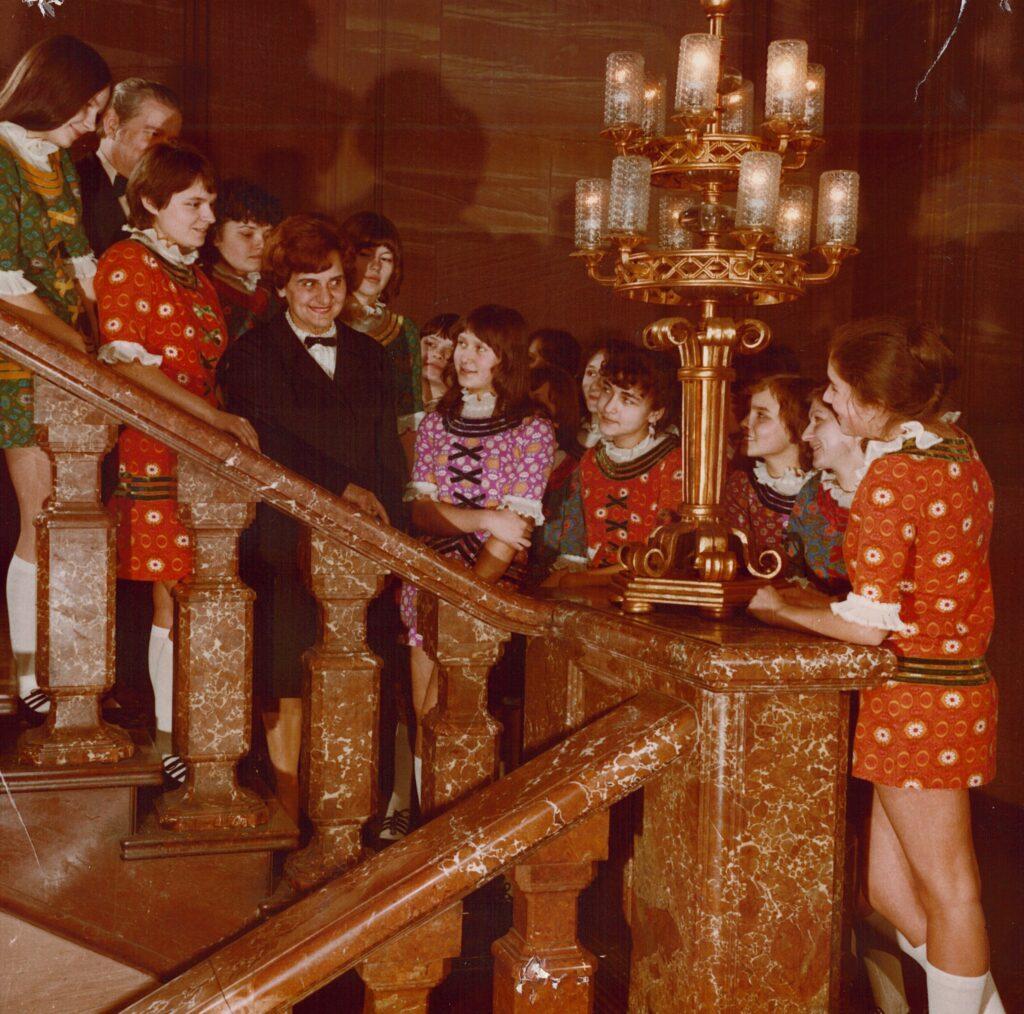 Na marmurowych schodach jednej z klatek schodowych Centrum Kultury ZAMEK stoi grupa dziewcząt i kobieta w czarnym kostiumie. Dziewczęta spoglądają na kobietę i uśmiechają się. Ubrane są w różnokolorowe sukienki w kwiaty.