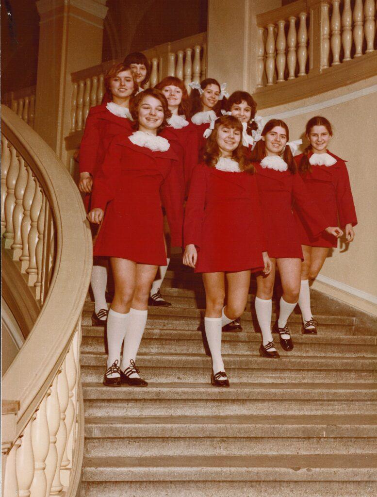 """Grupa dziewcząt z Chóru Dziewczęcego """"Skowronki"""" schodzi po marmurowych schodach zabytkowej klatki schodowej. Wszystkie ubrane są w jednakowe czerwone sukienki, białe podkolanówki i gustowne sceniczne trzewiki. Dziewczęta znajdują się w ruchu i uśmiechają się do obiektywu."""