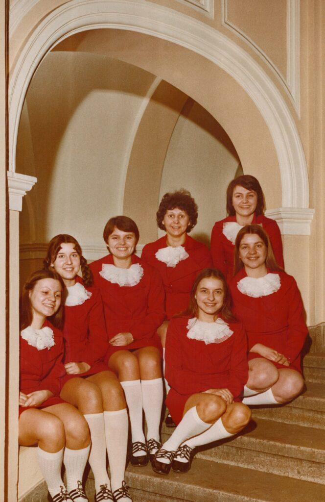 Na marmurowych schodach, we wnęce zabytkowej klatki schodowej siedzi siedem dziewcząt w jednakowych czerwonych sukienkach, białych podkolanówkach i gustownych scenicznych bucikach. Wszystkie uśmiechają się do obiektywu.