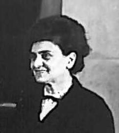 Czarno-białe zdjęcie przedstawia portret uśmiechniętej kobiety.