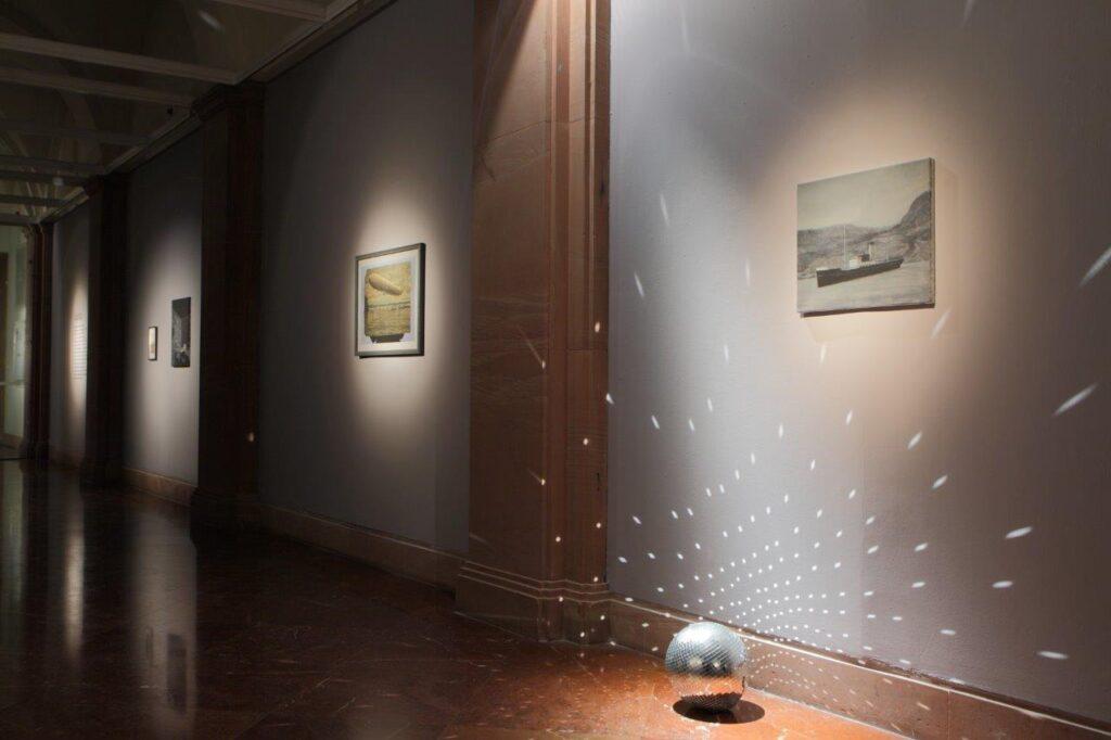 Zdjęcie przedstawia fragment ciemnej przestrzeni galerii z szarymi ścianami, na których wiszą prostokątne prace. Oświetlone są mocnym, punktowym światłem wydobywającym je z mroku. Po prawej stronie na podłodze stoi kula dyskotekowa, a odbijające się od małych lusterek na jej powierzchni światło tworzy efekt białych, świetlistych kropek.