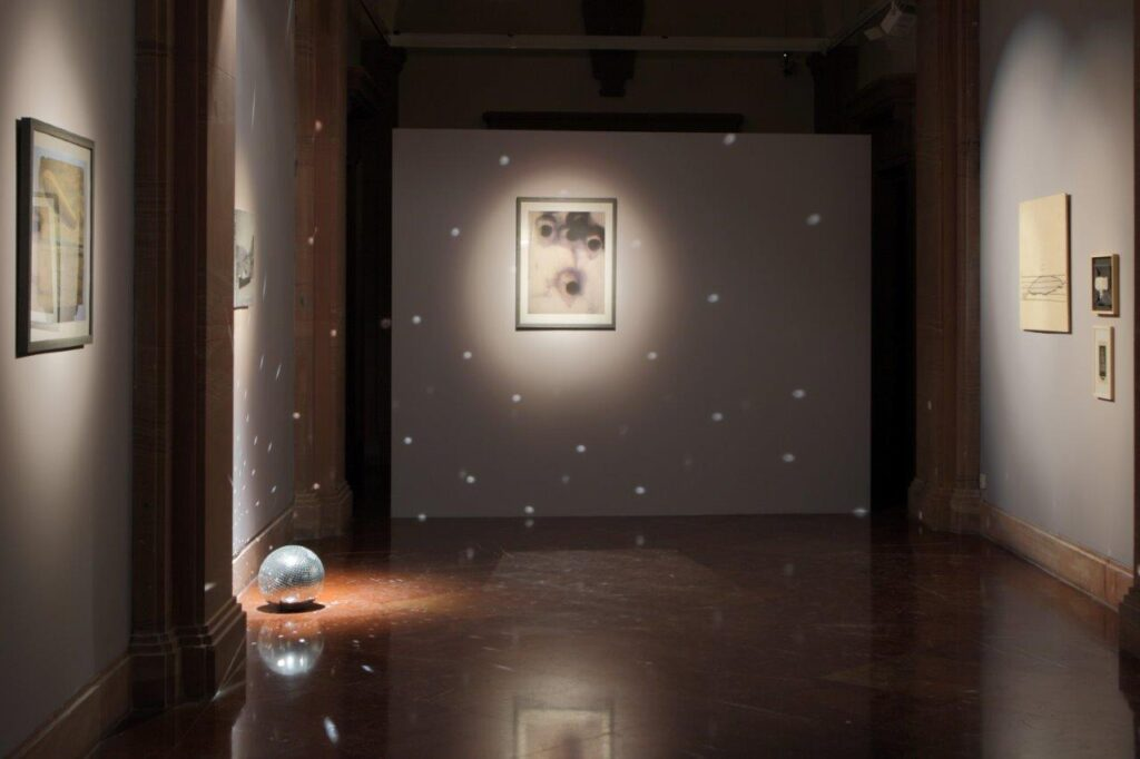 Zdjęcie przedstawia fragment ciemnej przestrzeni galerii, na szarych ścianach wisi sześć prostokątnych prac. Na ścianie na wprost znajduje się prostokątna praca oświetlona mocnym,  punktowym światłem wydobywającym ją z mroku. Po lewej stronie na podłodze znajduje się kula dyskotekowa, a odbijające się od małych lusterek na jej powierzchni światło tworzy efekt białych, świetlistych kropek.