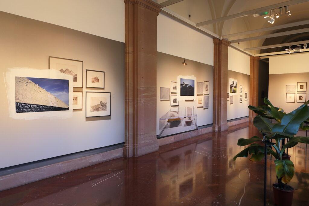 Zdjęcie przedstawia jasne wnętrze galerii, na ścianach której wylepione zostały tapety wydrukowane ze zdjęć wykonanych przez artystę w Los Angeles County Museum of Art (LACMA). Tapeta zamalowana została w kilku miejscach białą farbą, tworząc neutralne tło dla kolejnych, umieszczonych na niej fotografii. Wzdłuż okien galerii, po prawej stronie, stoją w donicach bananowce.