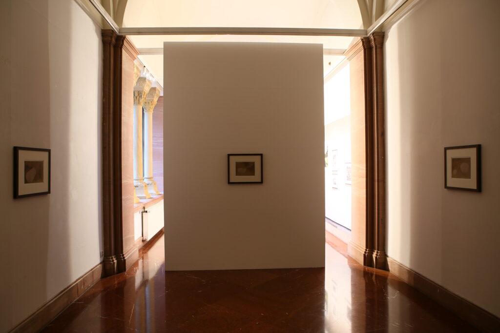 Zdjęcie przedstawia fragment wyciemnionej przestrzeni galerii. Na białych, nieoświetlonych ścianach wiszą trzy prace wykonane w technice salt-print, które powoli zanikały. Artysta wykonał je kilka lat wcześniej, wykorzystując oryginalną instrukcję napisaną przez twórcę tej techniki, Thomasa Wedgwooda, opublikowaną w 1798 roku. Przez lata, które minęły od czasu ich wykonania, odbitki te zdążyły już znacznie wyblaknąć, dlatego wymagały ochrony przed światłem.
