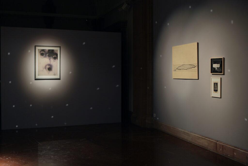 Zdjęcie przedstawia fragment ciemnej przestrzeni galerii. Na szarych ścianach wiszą cztery prostokątne prace. Na ścianie na wprost znajduje się prostokątna praca oświetlona punktowym światłem dającym efekt jasnej plamy oraz świetlistymi, jasnymi kropkami.