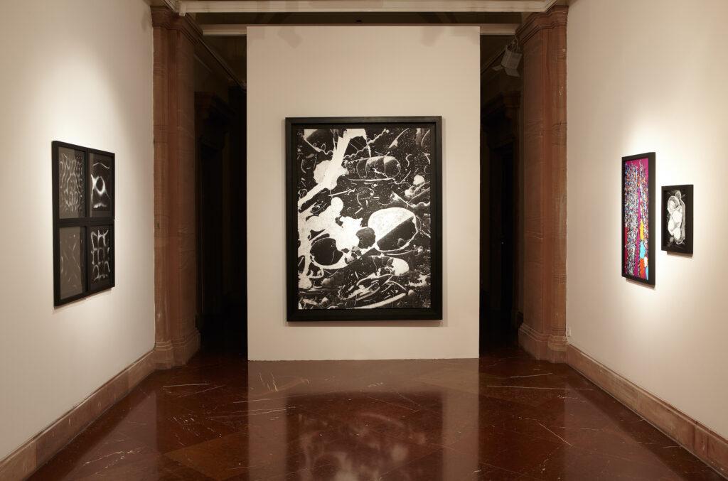 Zdjęcie przedstawia fragment wnętrza galerii. Na ścianie zamykającej przestrzeń galerii wisi wielkoformatowa czarno-biała fotografia. Po lewej stronie znajdują się cztery kwadratowe czarno-białe fotografie. Po prawej stronie wiszą obok siebie dwie fotografie, barwna i czarno-biała.