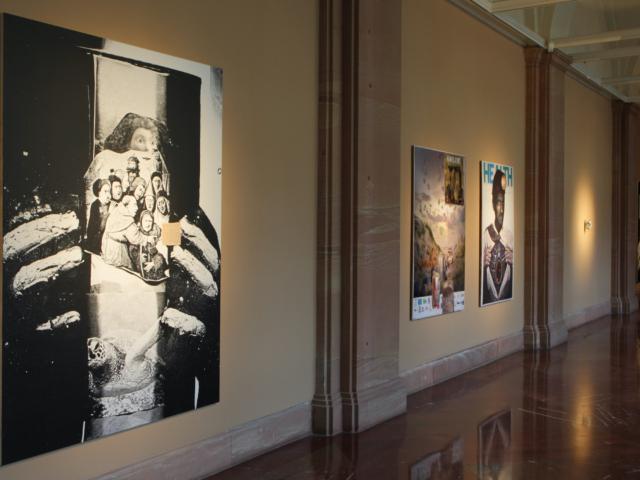 Zdjęcie przedstawia wnętrze galerii. Na ścianach w kolorze brązowym wiszą trzy wielkoformatowe prace. W głębi znajduje się powieszona na ścianie praca wykonana ze zgniecionej puszki po napoju gazowanym oświetlona ostrym, punktowym światłem.