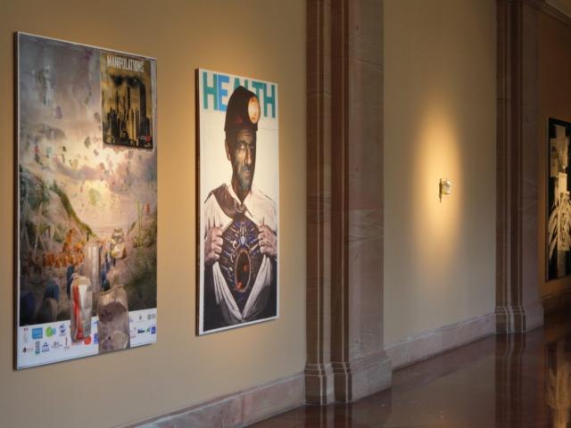 Zdjęcie przedstawia zbliżenie na fragment galerii. Trzy wielkoformatowe prace oraz praca wykonana ze zgniecionej puszki po napoju gazowanym wiszą na ścianach w kolorze brązowym. Wszystkie obiekty oświetlone są ostrym, punktowym światłem.