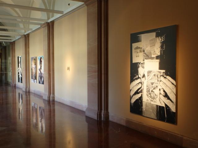 Zdjęcie przedstawia przestrzeń galerii ukazaną z jej wnętrza w kierunku wyjścia. W tle znajdują się szklane drzwi. Na ścianie, po prawej stronie fotografii wiszą cztery wielkoformatowe prace oraz praca wykonana ze zgniecionej puszki po napoju gazowanym. Wszystkie obiekty oświetlone są ostrym, punktowym światłem.