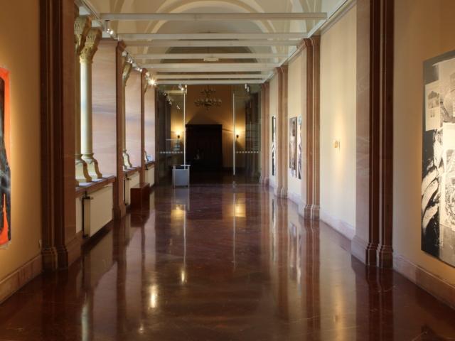 Zdjęcie przedstawia przestrzeń galerii ukazaną z jej wnętrza w kierunku wyjścia. W tle znajdują się szklane drzwi oraz duża drewniana ława. Po prawej i lewej stronie, na ścianach, wiszą jedna obok drugiej wielkoformatowe prace.