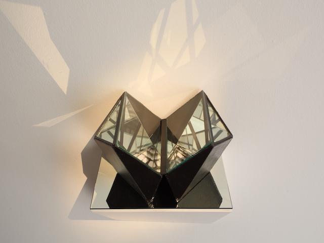 Zdjęcie przedstawia obiekt-rzeźbę o kształcie przypominającym geometryczną formę serca. Obiekt zbudowany jest z luster odbijających i załamujących światło, którego refleksy padają na płaszczyznę ściany. Całość ustawiona jest na lustrzanej półce przymocowanej do białej ściany.