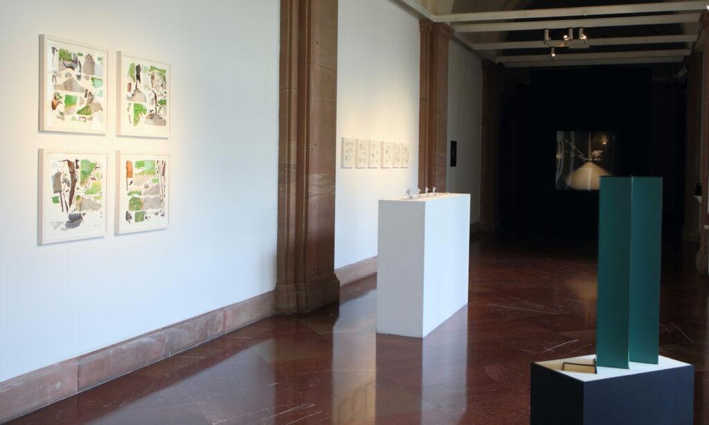 Zdjęcie przedstawia jasne wnętrze galerii. Na białych ścianach po lewej stronie oraz czarnej ścianie w głębi galerii wiszą fotografie. Pośrodku przestrzeni ustawione są dwa postumenty − biały i czarny − ze stojącymi na nich obiektami.