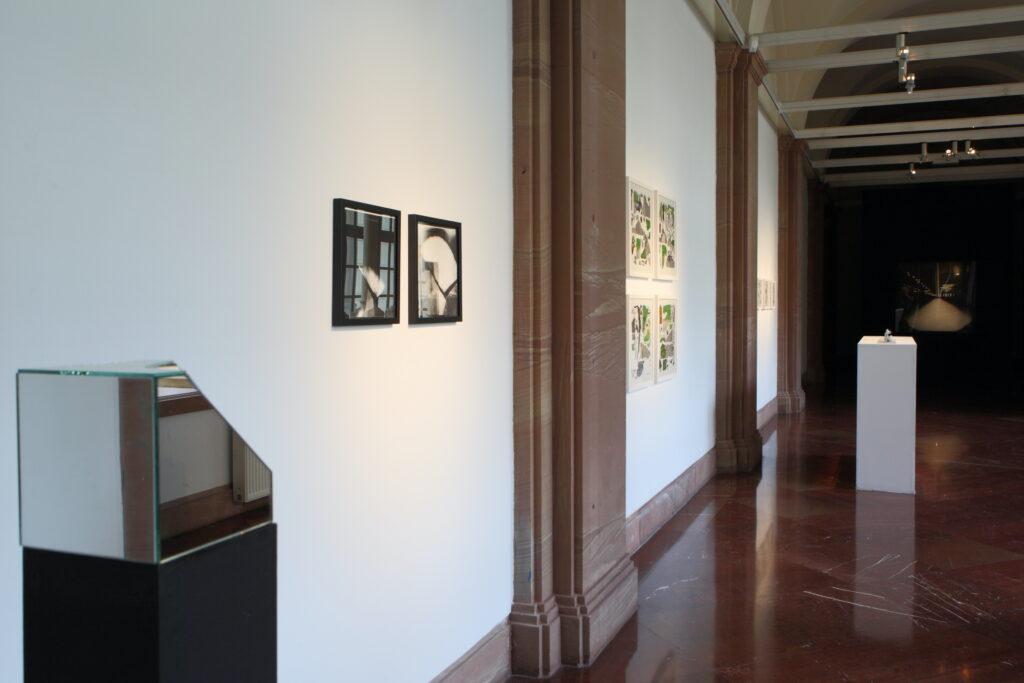 Zdjęcie przedstawia jasne wnętrze galerii. Na pierwszym planie, po lewej stronie, na czarnym podeście przy ścianie stoi przestrzenny obiekt zbudowany z luster. Na białej ścianie prowadzącej w głąb galerii wiszą fotografie. Perspektywę zamyka czarna ściana z dużą czarną fotografią, od której odcina się biały postument ustawiony pośrodku galerii.