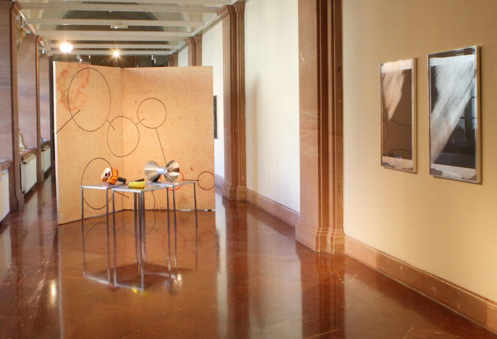 Zdjęcie przedstawia jasne wnętrze galerii. W głębi znajduje się przestrzenna instalacja z umieszczoną na niej ilustracją z graficznym rysunkiem przedstawiającym geometryczne kształty, koła i linie. Przed nią ustawione są metalowe stoliki z leżącymi na nich przestrzennymi obiektami wykonanymi z błyszczących materiałów używanych do budowy statków kosmicznych. Po prawej stronie na ścianie wiszą dwie prostokątne fotografie.