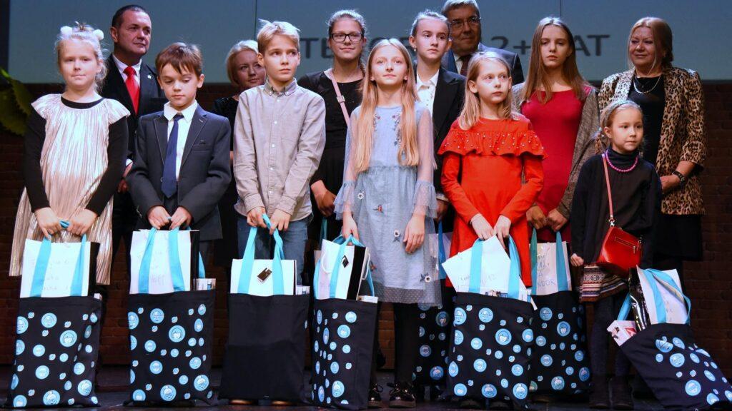 Zdjęcie grupowe. Dziewięcioro dzieci - laureatów konkursu oraz czterech organizatorów.