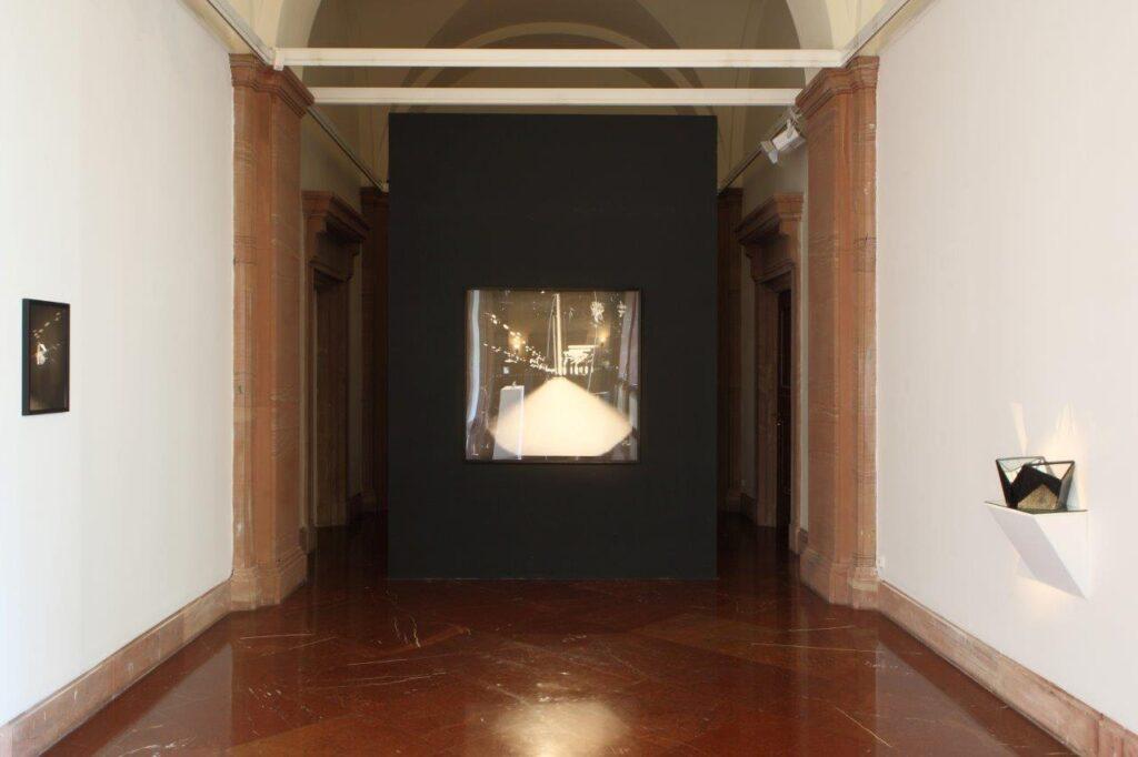 Zdjęcie przedstawia jasne wnętrze galerii. W tle znajduje się czarna ściana z powieszoną na niej wielkoformatową, kwadratową czarno-białą fotografią. Po prawej stronie na białej ścianie, na półce umieszczony jest obiekt zbudowany z luster odbijających i załamujących światło, którego refleksy padają na płaszczyznę ściany. Po prawej stronie na białej ścianie wisi czarno-biała fotografia.