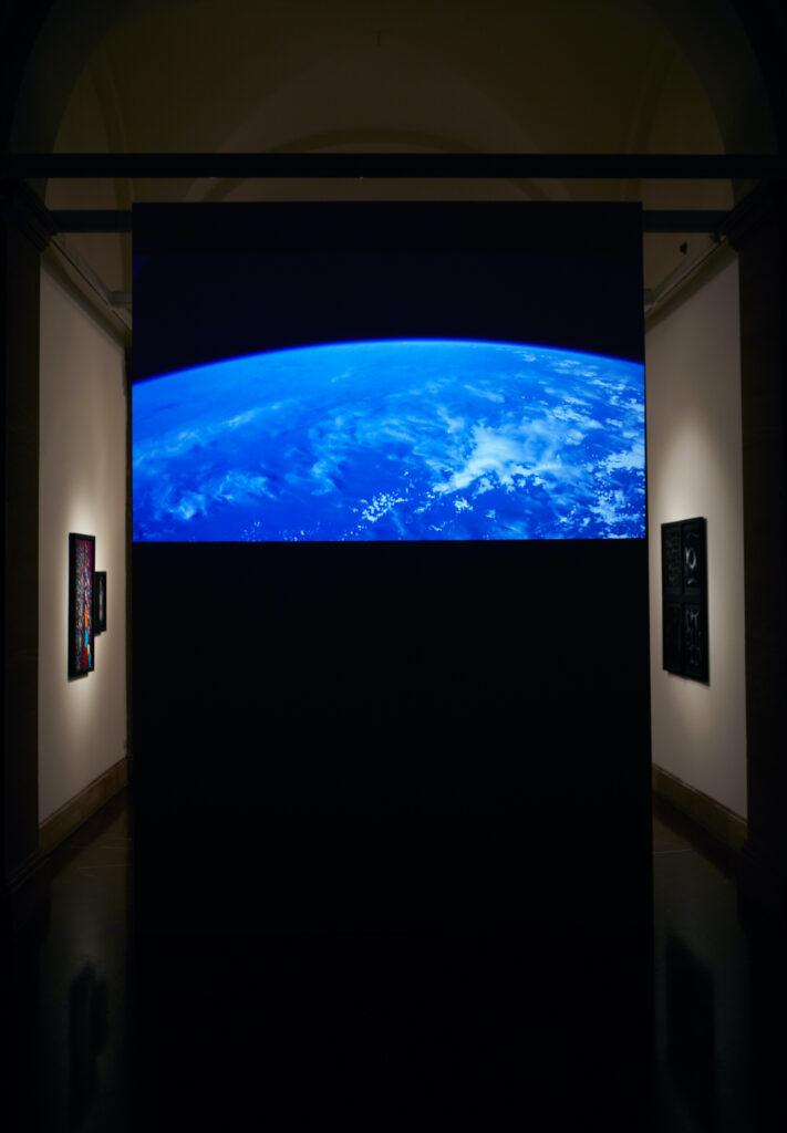 Fotografia przedstawia ścianę z wyświetloną na niej projekcją przedstawiającą widok fragmentu Ziemi widzianej z kosmosu. Była to projekcja wyświetlana na żywo, w czasie rzeczywistym, ze stacji kosmicznej NASA. Pierwszy plan jest ciemny i dominuje na nim błękitny kolor wyświetlanej powierzchni planety. Po bokach, w tle, za ścianą z projekcją wyłaniają się wiszące na białych ścianach, oświetlone punktowym światłem fotografie.