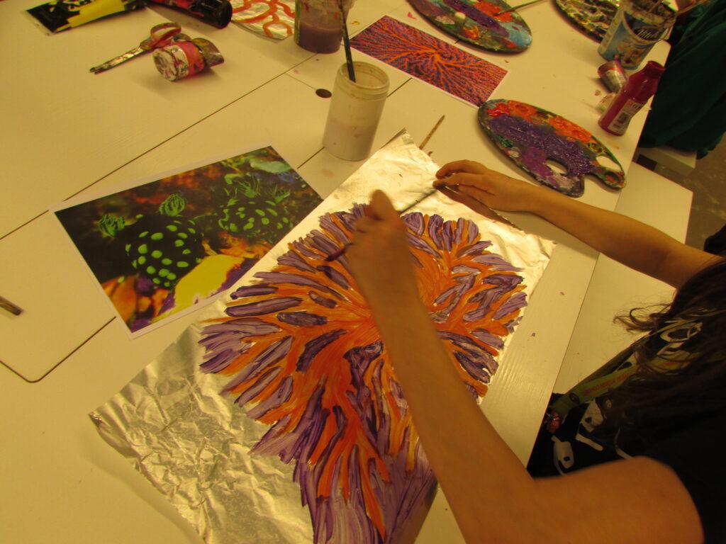 Zdjęcie zostało wykonane podczas warsztatów malarstwa na folii, których tematem były morskie głębiny. Widzimy na nim ręce dziecka malującego ukwiały na folii.