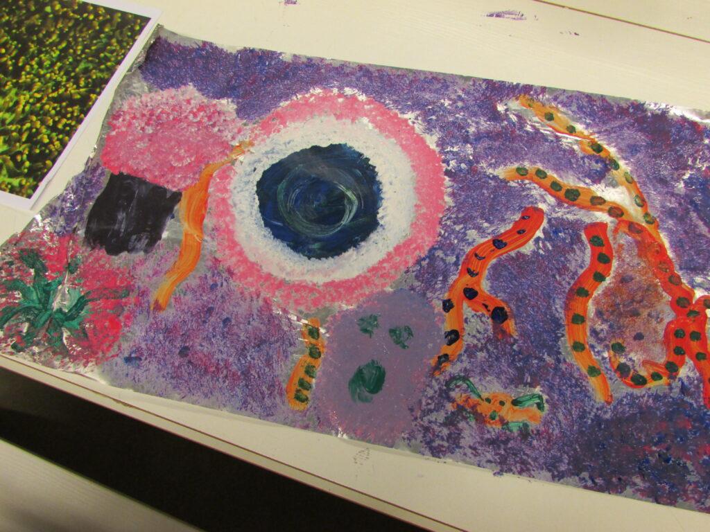 Na zdjęciu widzimy pracę wykonaną, która przedstawia. Praca utrzymana jest w intensywnych barwach: fioletu, różu, pomarańczy i zieleni.