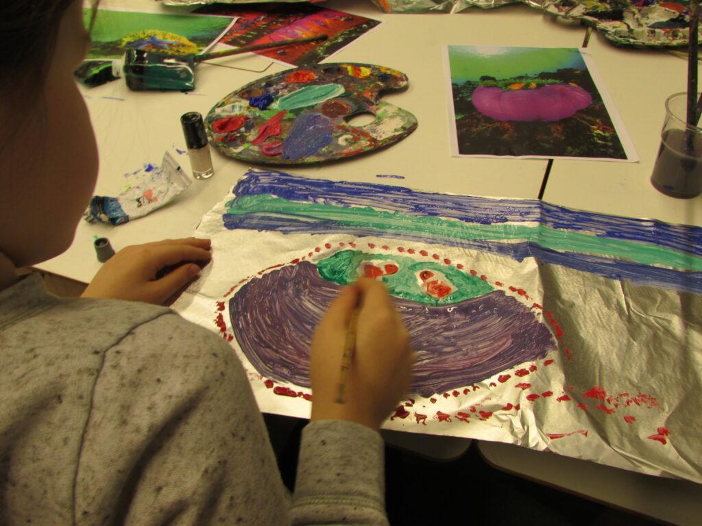 Fotografia została wykonana podczas warsztatów malarstwa na folii przy użyciu temper. Przedstawia dziewczynkę siedzącą, widzianą od tyłu, która maluje przy stole maluje na folii morskiego stwora.