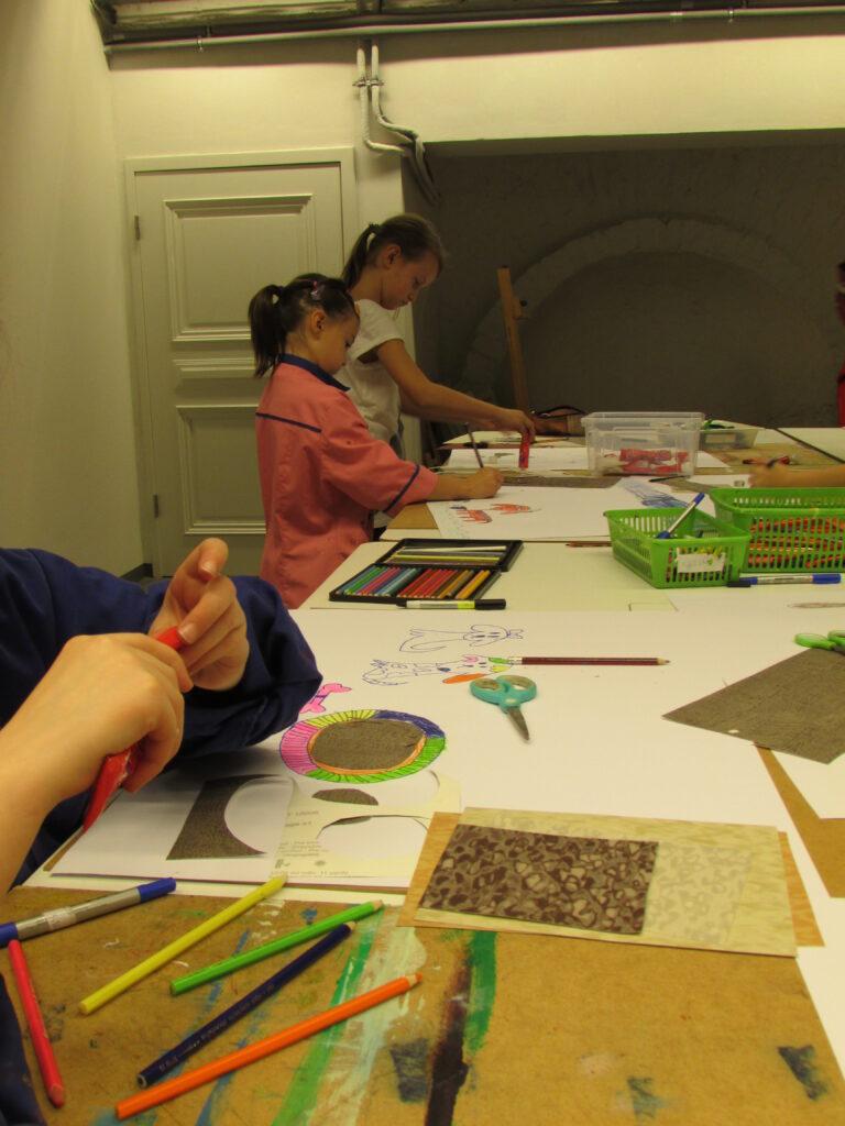 Na zdjęciu widzimy długi stół, przy którym troje dzieci tworzy obrazy podczas warsztatów  techniki mieszanej. Dziecko znajdujące się najbliżej nie jest w pełni widoczne, widać tylko jego ręce.