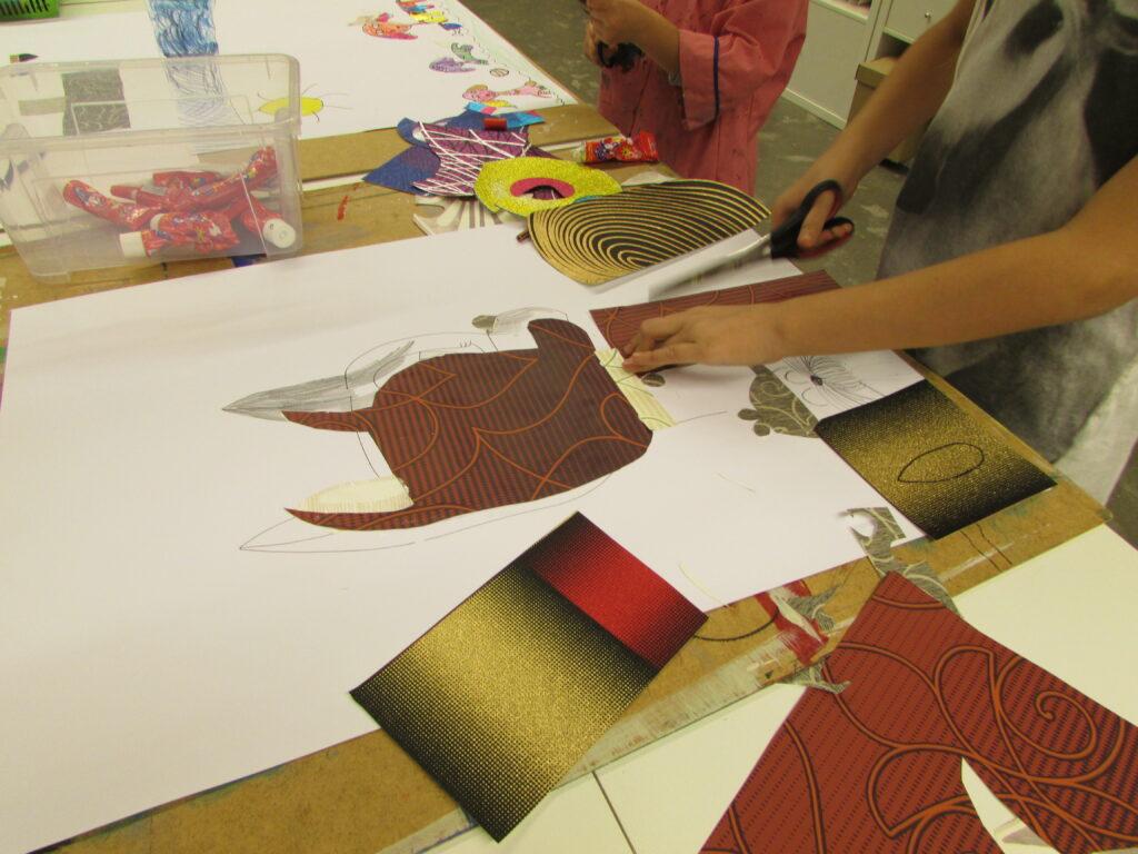 Fotografia przedstawia dziecko wycinające kształty z kolorowego papieru, które następnie przykleja do białego brystolu tworząc w ten sposób obraz. Postać jest ucięta, widać jedynie jej poruszone dłonie i fragment tułowia.