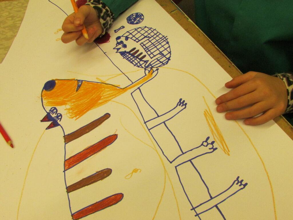 Na fotografii widzimy ręce dziecka, które rysuje psa kredkami ołówkowymi. Praca została wykonana techniką mieszaną.