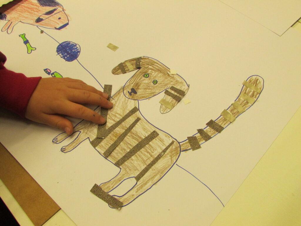 Na zdjęciu widzimy wizerunek narysowanego psa oraz dziecięcą rękę, która przykleja na tułów zwierzęcia paski kolorowego papieru. Praca powstała podczas warsztatu w technice mieszanej.