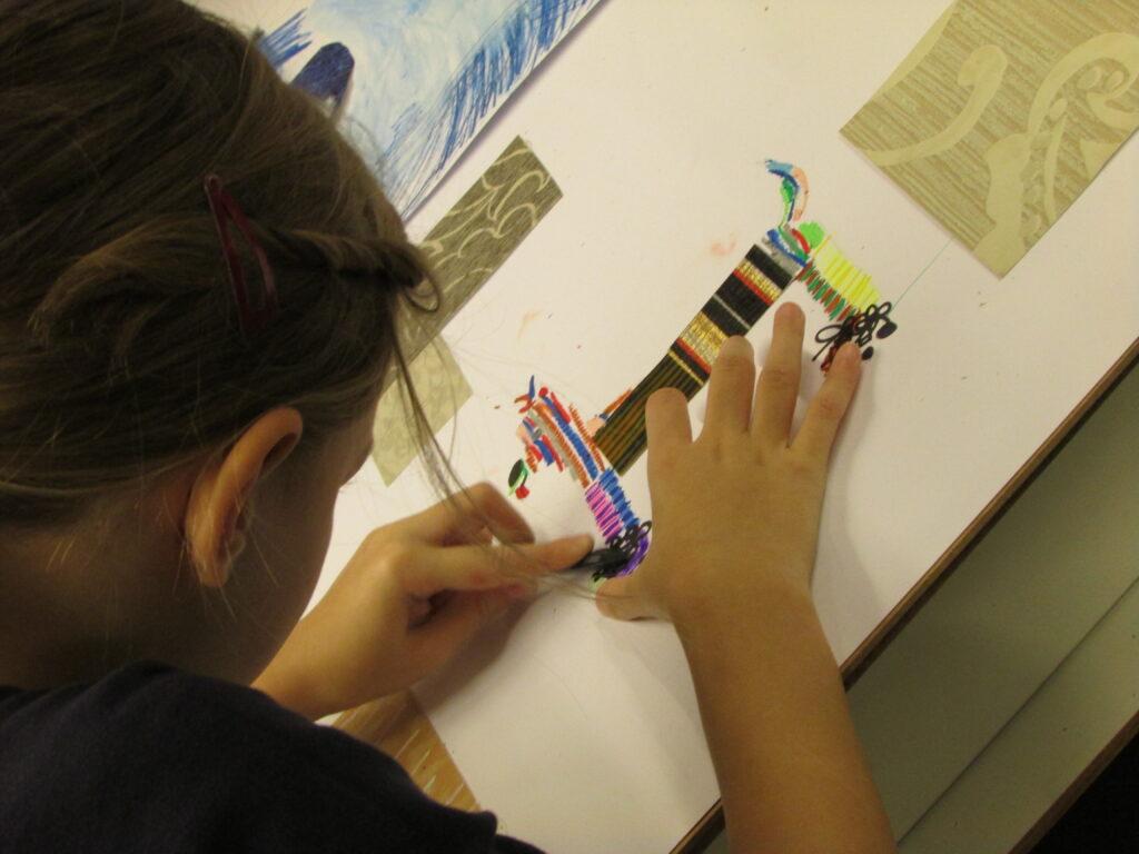 Na zdjęciu widzimy dziecko nachylające się nad swoją pracą przedstawiającą psa o umaszczeniu w wielokolorowe paski. Fotografia została wykonana podczas warsztatu w technice mieszanej.