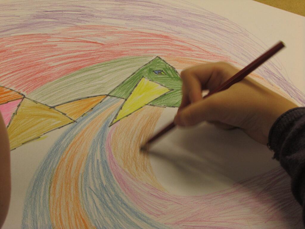 Na zdjęciu widzimy poruszoną dłoń dziecka rysującego kredką swoją wielokolorową pracę. Fotografia została wykonana podczas warsztatu w technice kredek ołówkowych.
